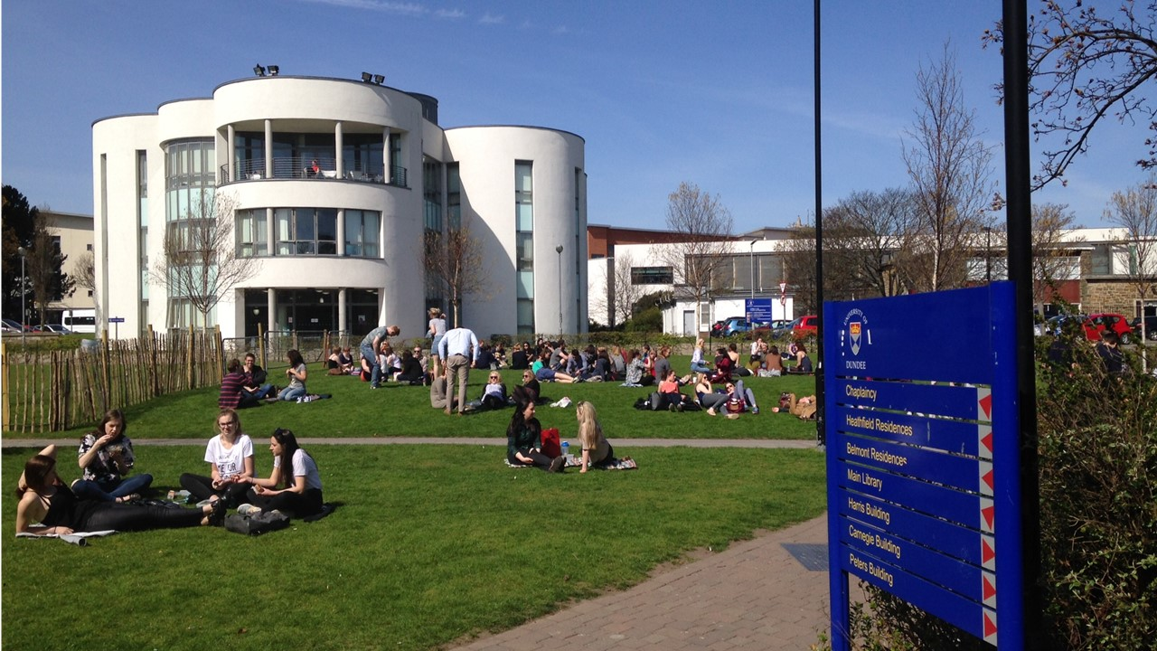 Students on Campus Green grass outside Enquiry Centre