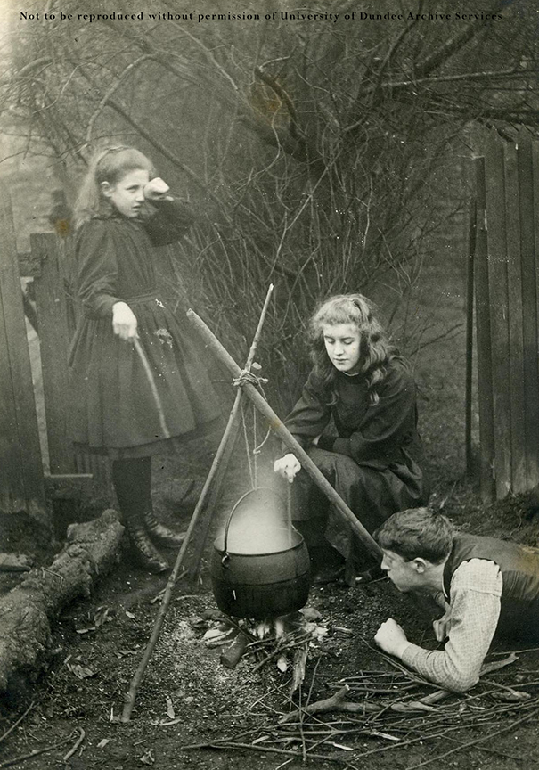 Pirie children, Margaret, Nell and Sandy, thought to be Dr George Alexander Pirie, c1885 sitting at a fire and cauldron.