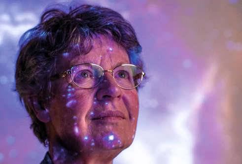 Professor Dame Jocelyn Bell Burnell with image of a galaxy