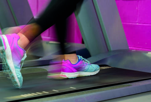 The feet of a person running on a treadmill with motion blur