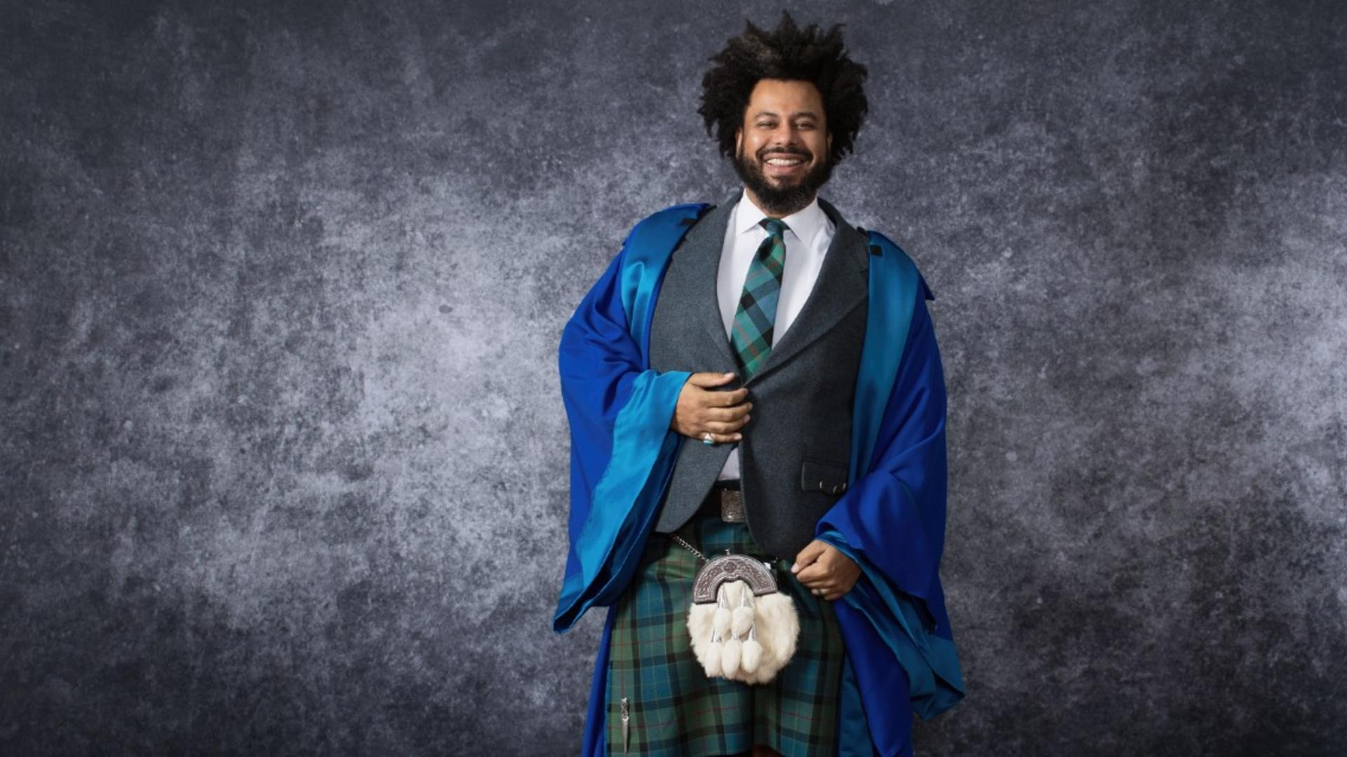 Johnathan Wilson in his graduation gown in front of a textured background