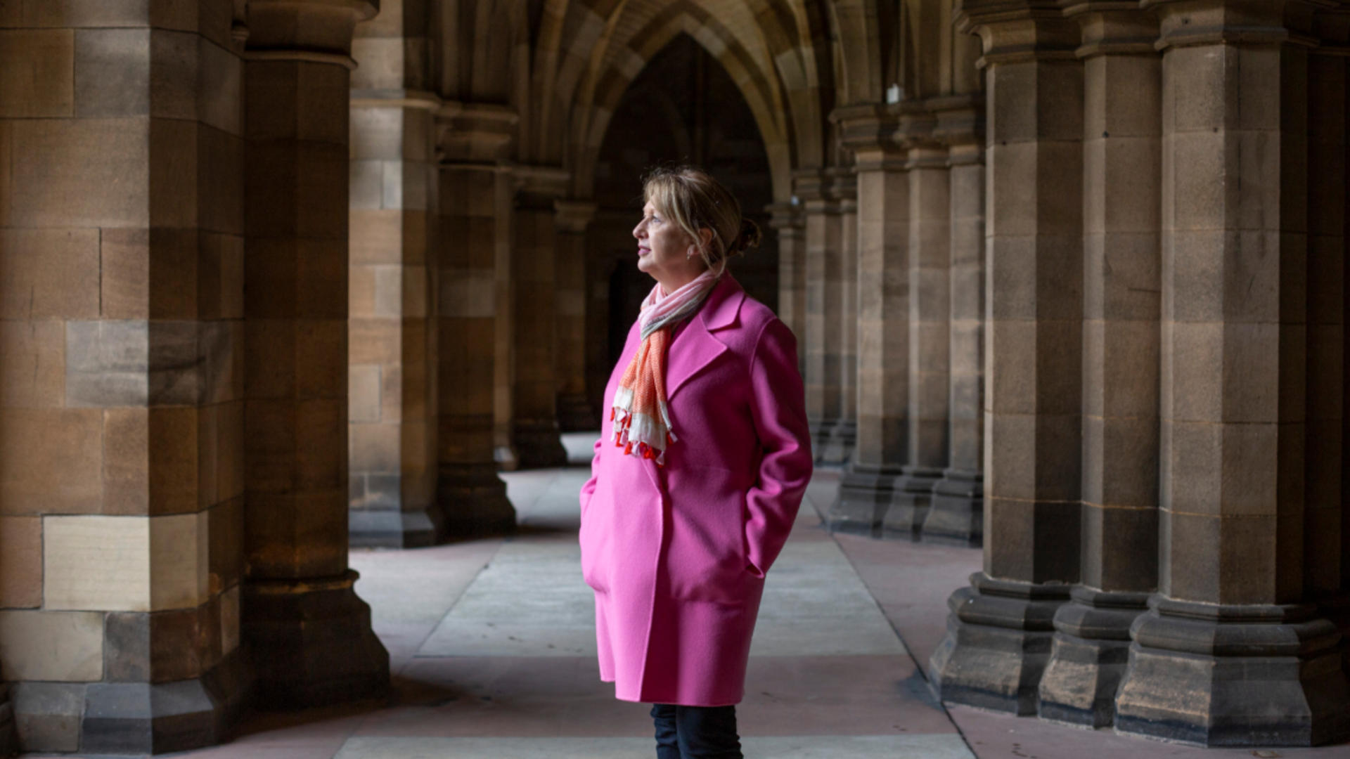 Mary McAleese standing between pillars with a romanesque arch in the background