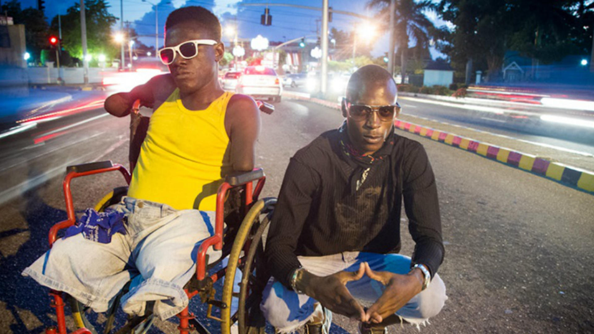 Two men, one in a wheelchair, pose in a busy roadway at night